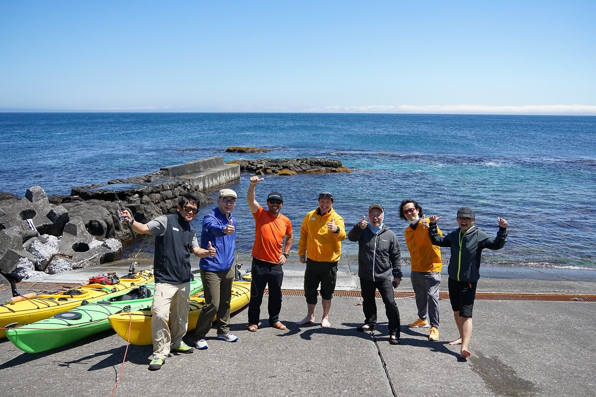 A group of kayakers poses by the sea