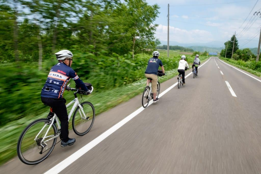 A guided cycling tour rides along a rural road surrounded by greenery.