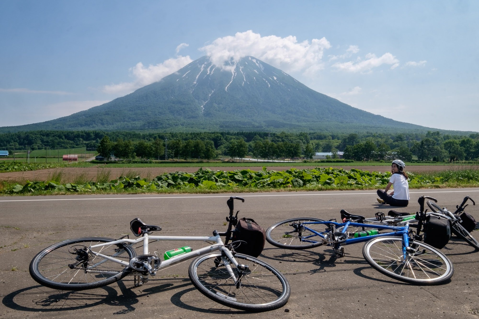 A cyclist takes a break in front of Mount Yotei whilst on a cycling tour.